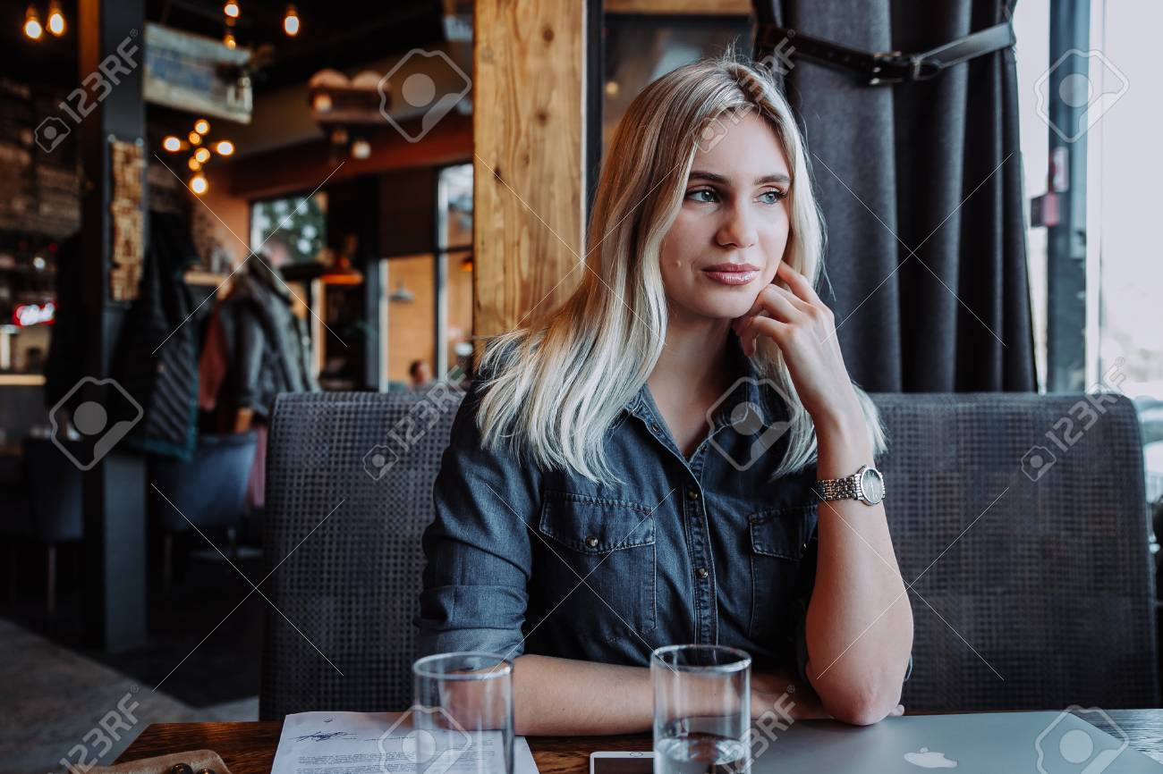 beautiful young woman sitting at table with laptop and looking at window in cafe - 97933691