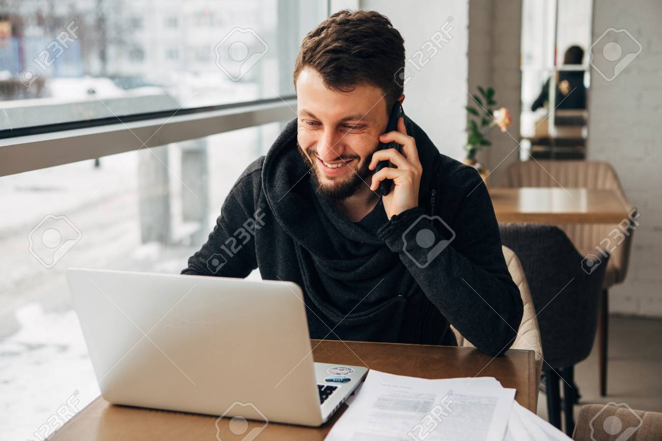 a young businessman talking on the phone and working at a laptop in a cafe - 97567505