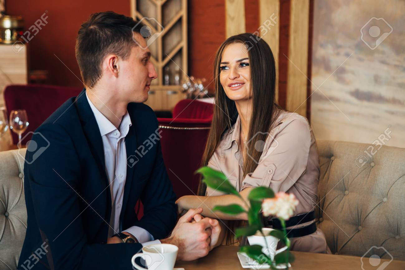Happy young couple taking selfie with smart phone at cafe - 97567347