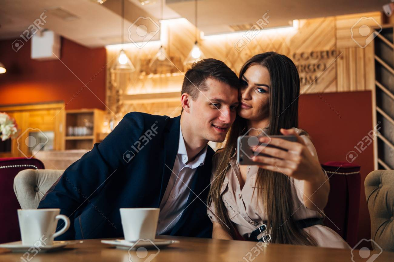 Happy young couple taking selfie with smart phone at cafe - 97567453