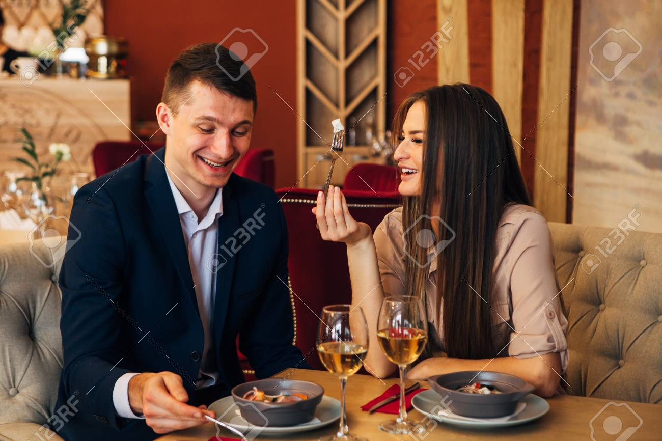 happy couple having dinner at restaurant and laughing - 97567471