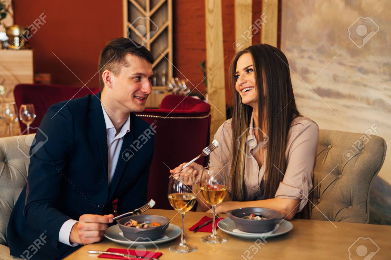 smiling couple having dinner and drinking white wine at date in restaurant - 97567473