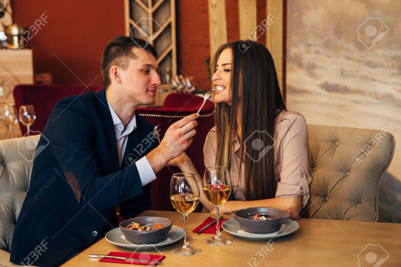 a man feeds his woman in a restaurant - 97567474