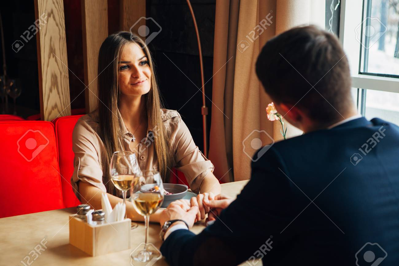Young happy couple romantic date drink glass of white wine at restaurant, celebrating valentine day - 97567479