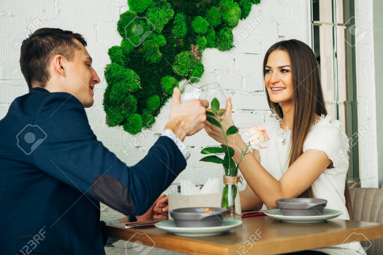 smiling couple having dinner and drinking white wine at date in restaurant - 97567493