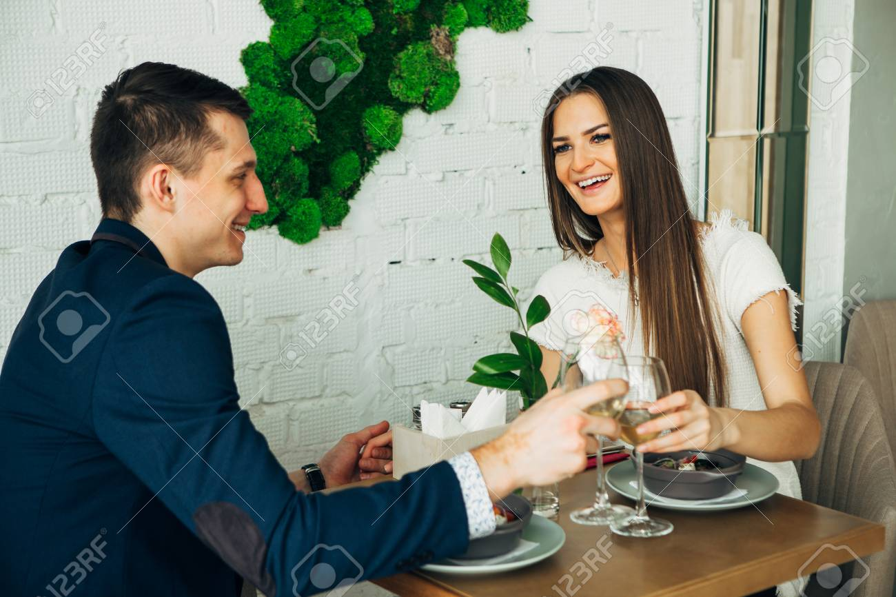 smiling couple having dinner and drinking white wine at date in restaurant - 97567494