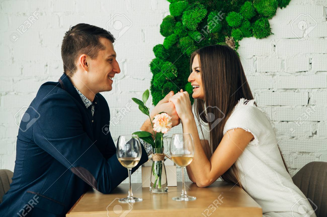 Cheerful young man and woman are dating in restaurant. They are sitting at the table and looking at each other with love. - 97567498