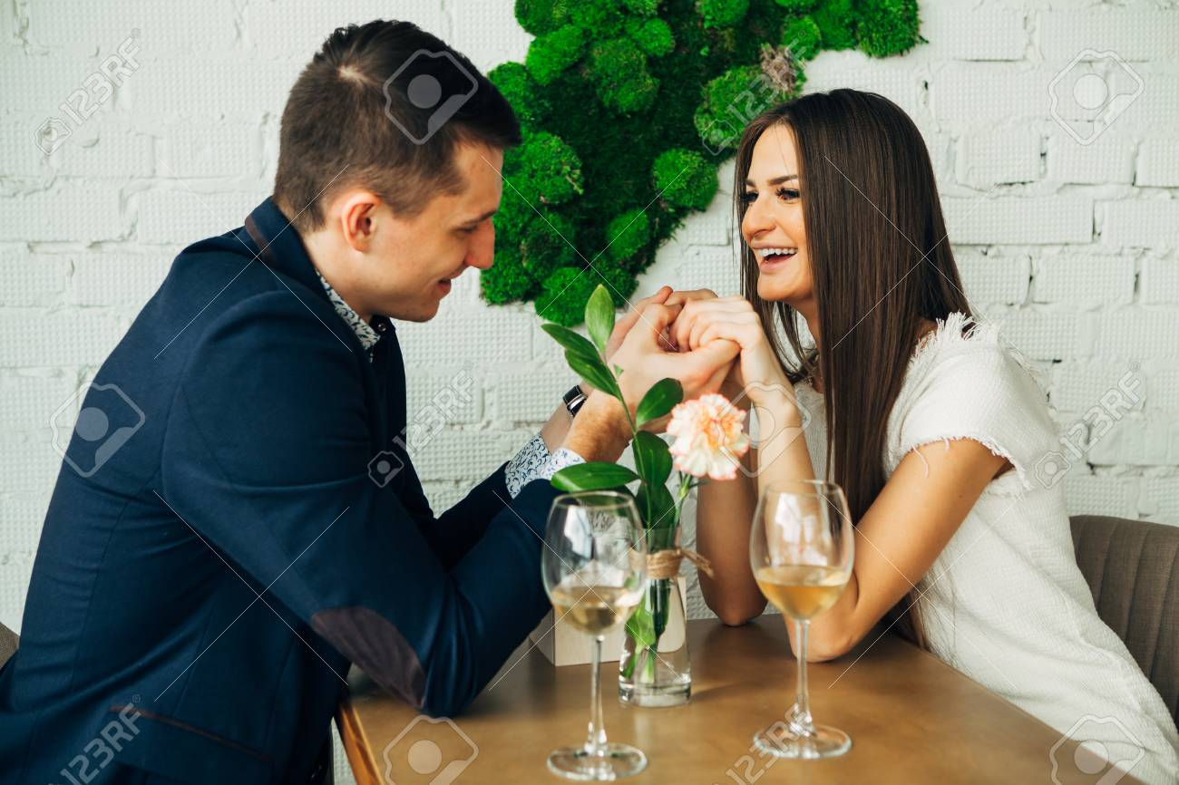 Cheerful young man and woman are dating in restaurant. They are sitting at the table and looking at each other with love. - 97567500