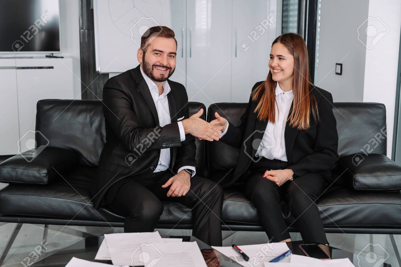 Business handshake at meeting or negotiation in the office. Partners are satisfied because signing contract or financial papers - 143127810