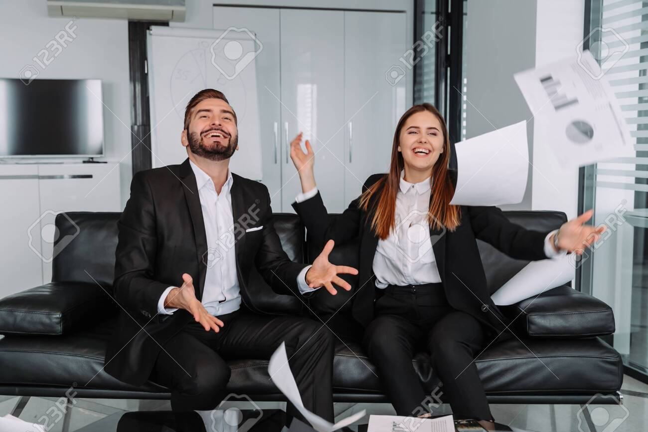 happy colleagues throwing business papers in modern office - 143127728