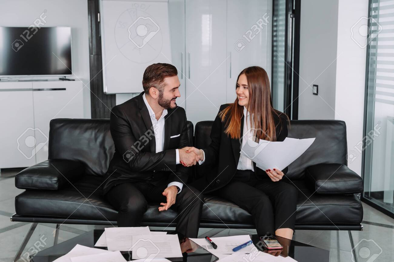 Man and a woman in a casual setting shake hands at the conclusion of the deal. - 143127983