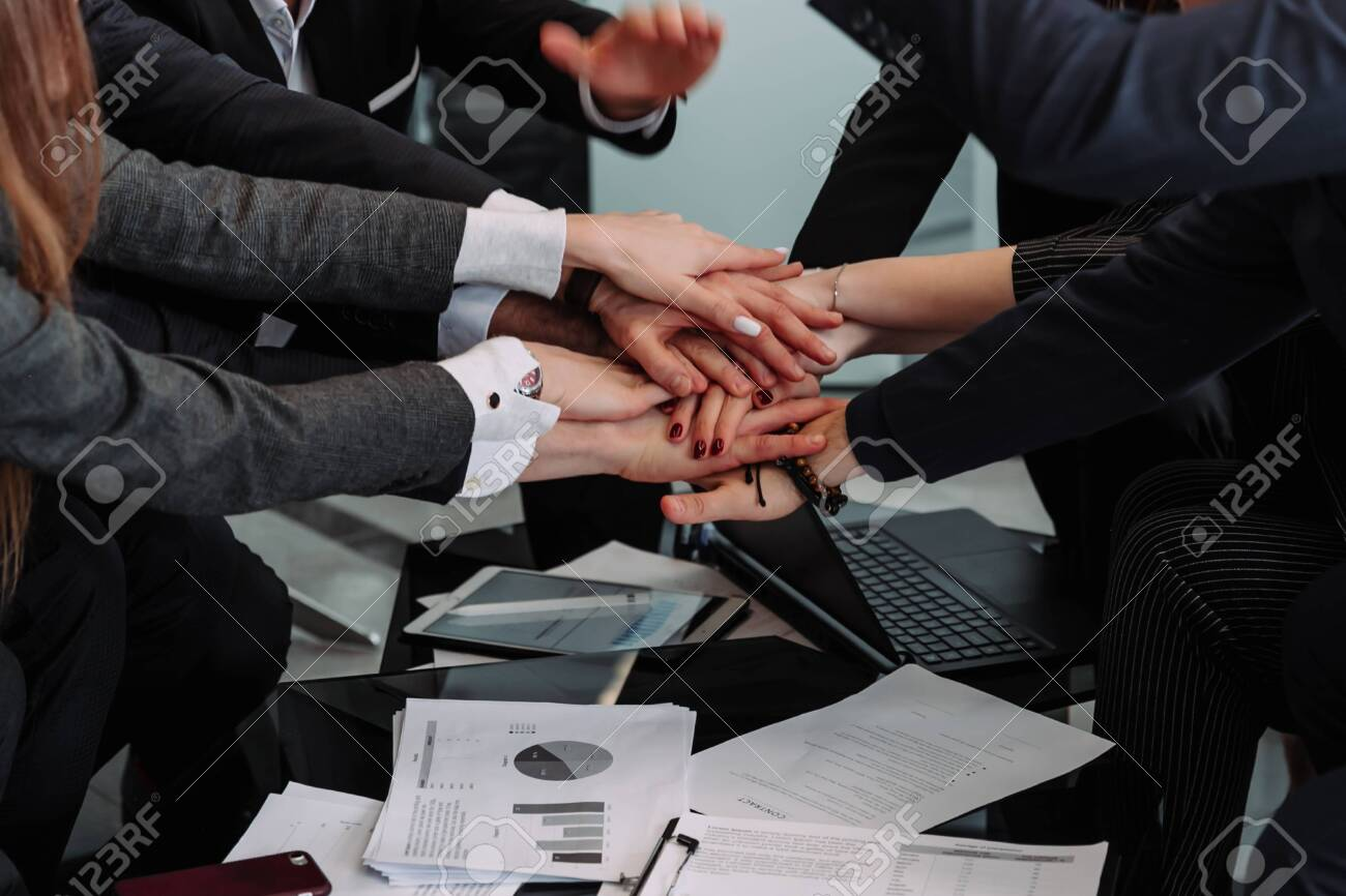 diverse workers or employees put hands in stack showing support and unity, reach shared goal together, people engaged in teambuilding activity or training. Teamwork concept - 143046096