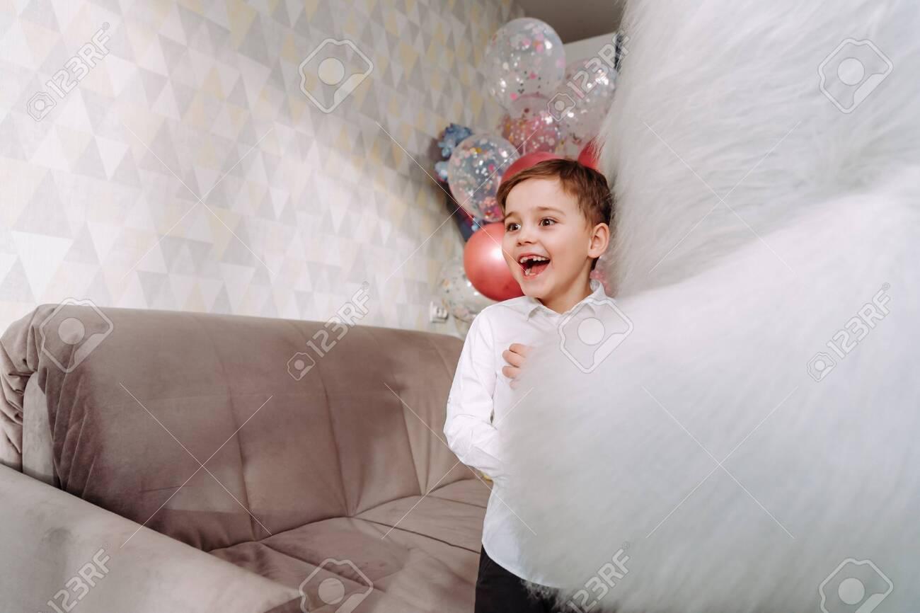 a boy hugs a big bear at hone on party - 145783968