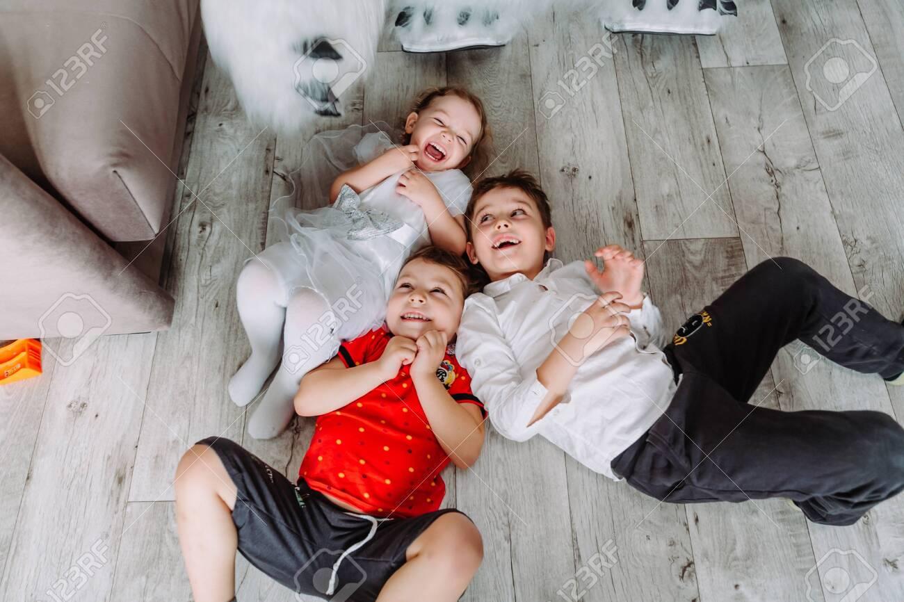 Cute little children having fun, lying on the floor in kindergarten - 145783998