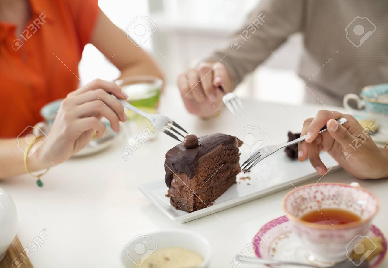 stock photo women sharing slice of cake