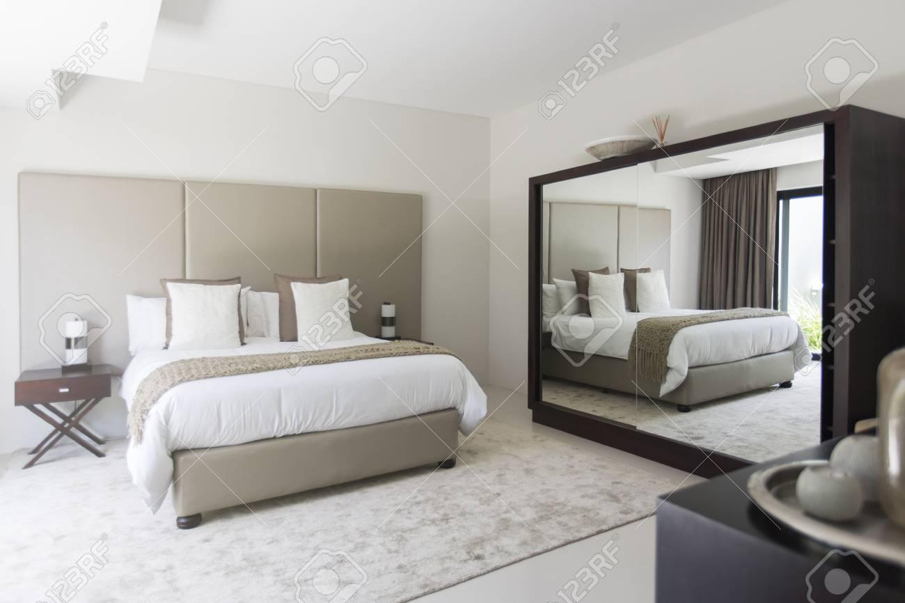 Camera da letto moderna bianca e beige con letto matrimoniale specchio
