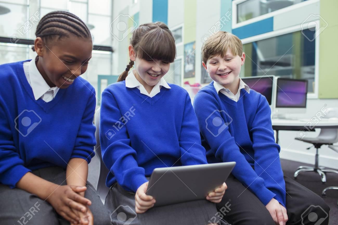 355fc4550e131 Foto de archivo - Niños de escuela primaria vistiendo uniformes escolares  azules con tableta digital y sonriendo en el aula