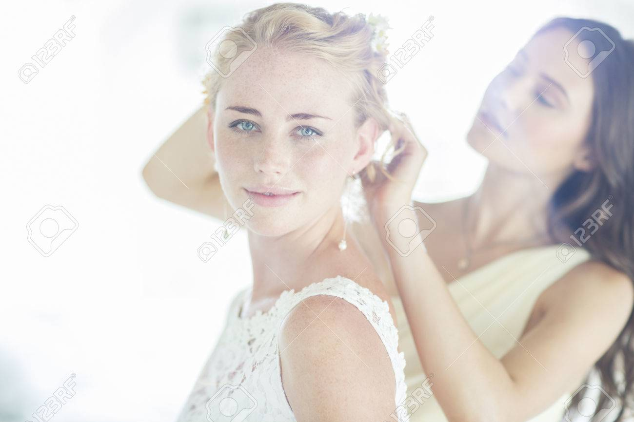 Bridesmaid Helping Bride With Hairstyle In Domestic Room Stock Photo ...