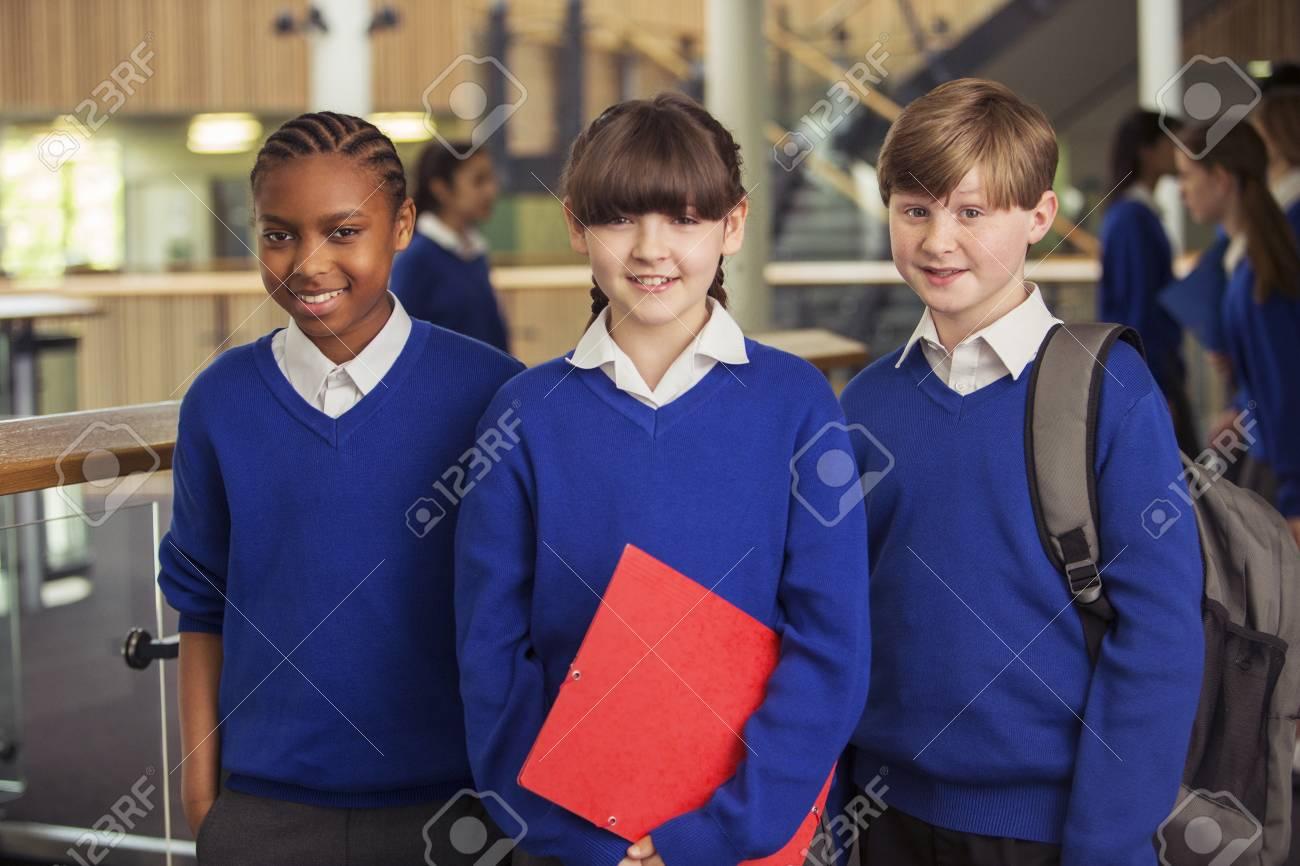 982a16aeb77c2 Foto de archivo - Retrato de tres niños de escuela primaria vistiendo uniformes  escolares azules de pie en el pasillo