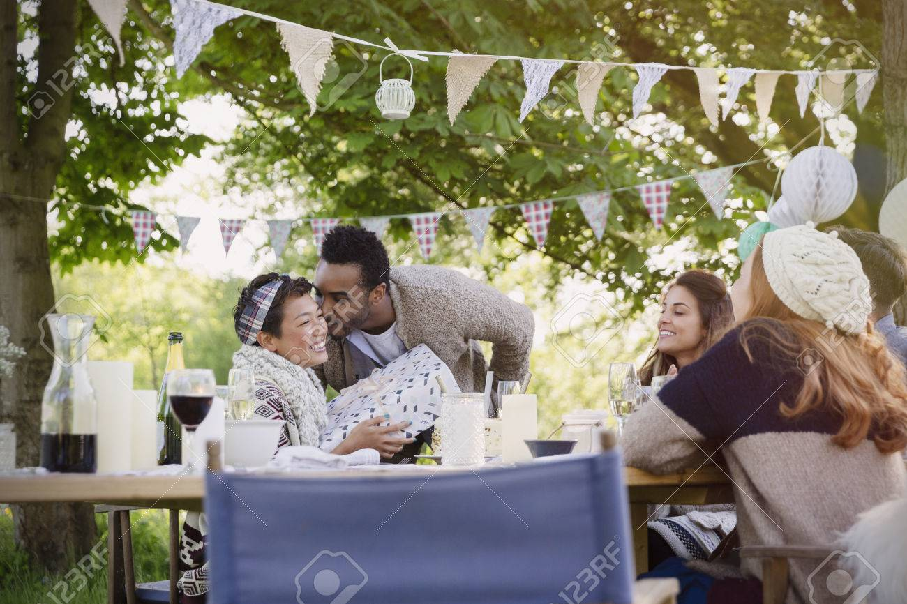 Boyfriend Kissing Girlfriend With Birthday Gift At Garden Party Table Stock Photo