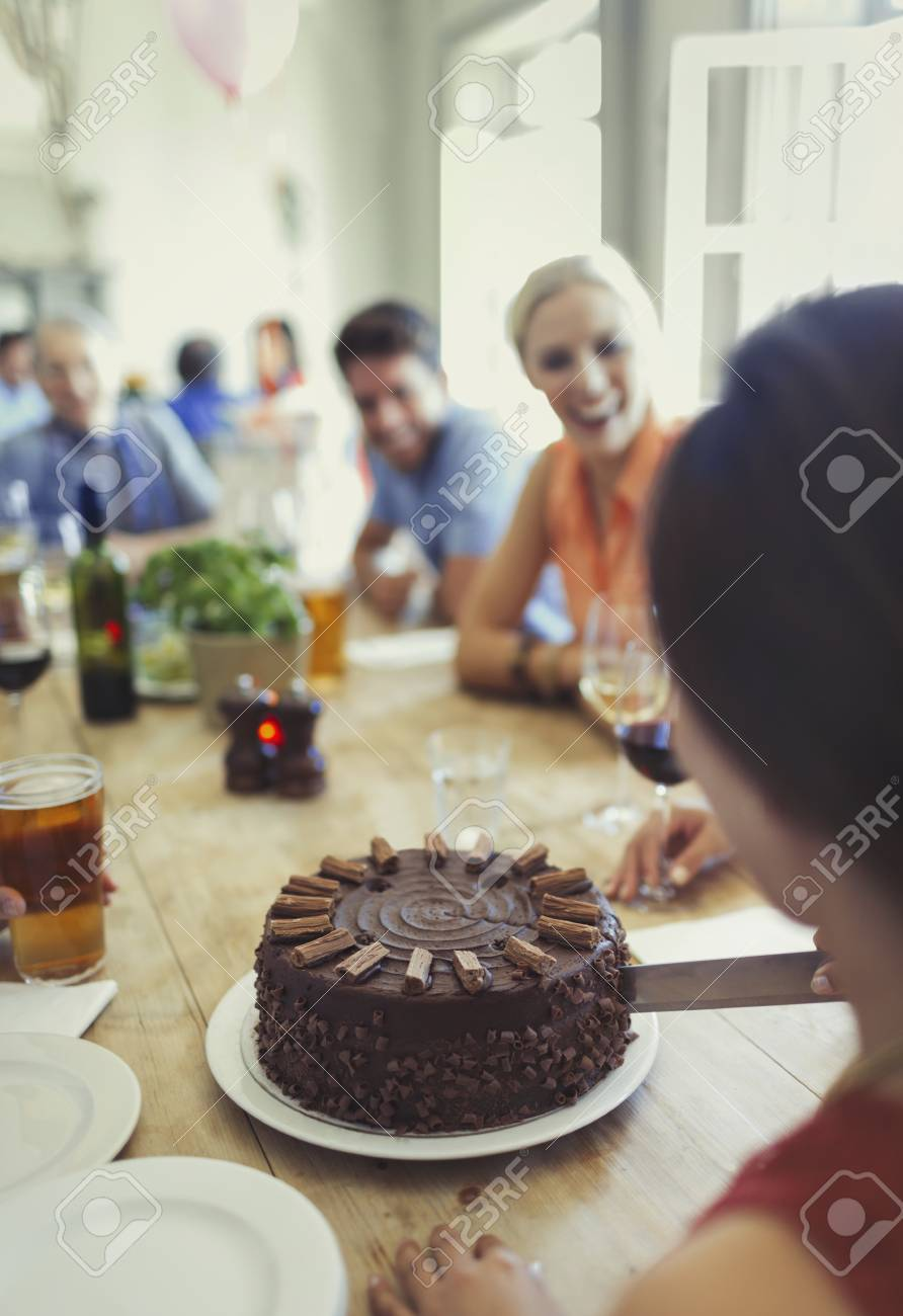 Woman Cutting Chocolate Birthday Cake With Friends At Restaurant