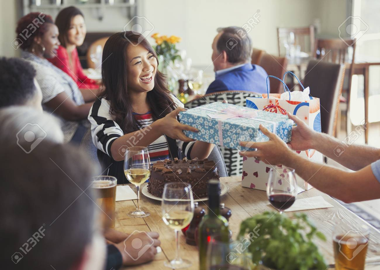 Smiling Woman Receiving Birthday Gift From Friend At Restaurant Table Stock Photo