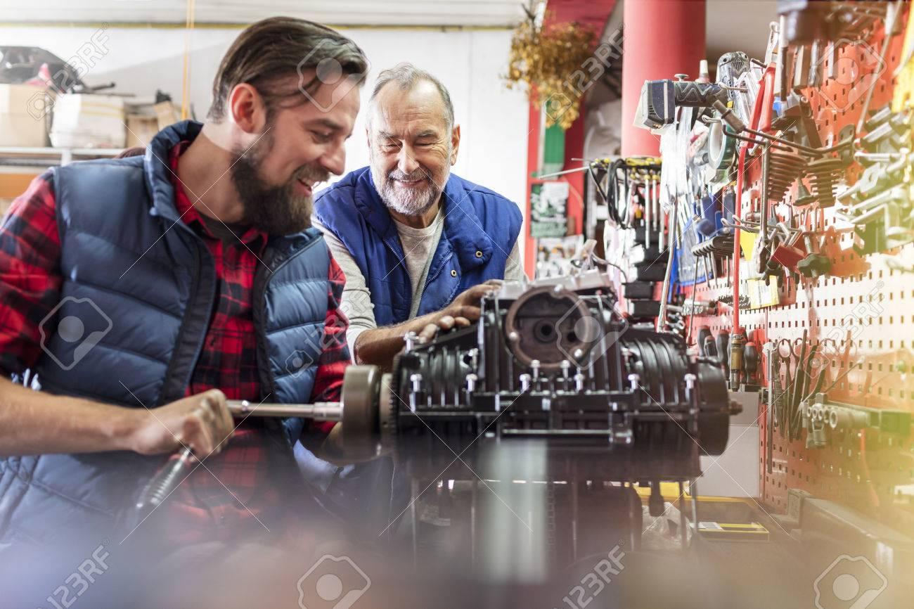 male motorcycle mechanics repairing engine in workshop stock photo 81393581