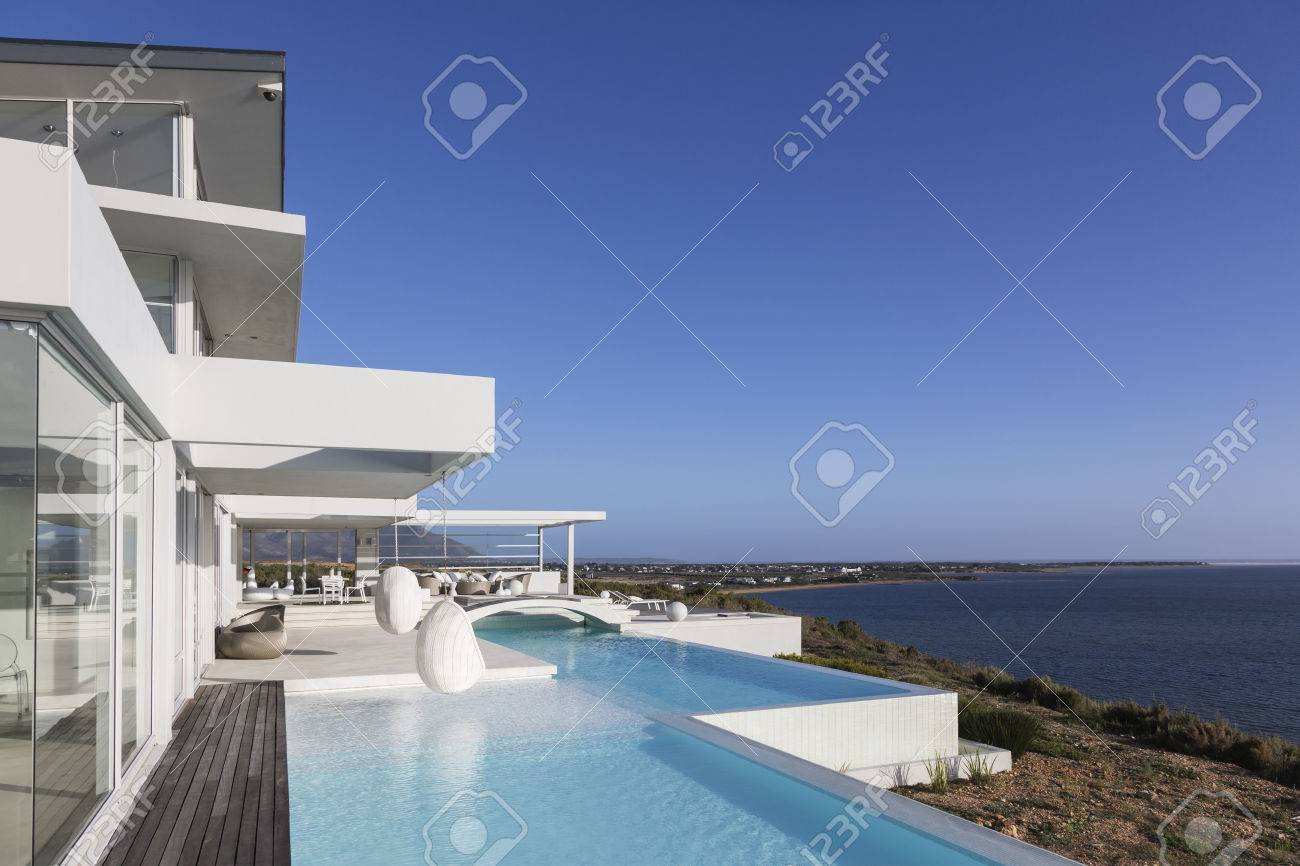 Ensoleillé, calme moderne extérieur de la maison de luxe de luxe avec  piscine à débordement et vue sur l\'océan sous le ciel bleu