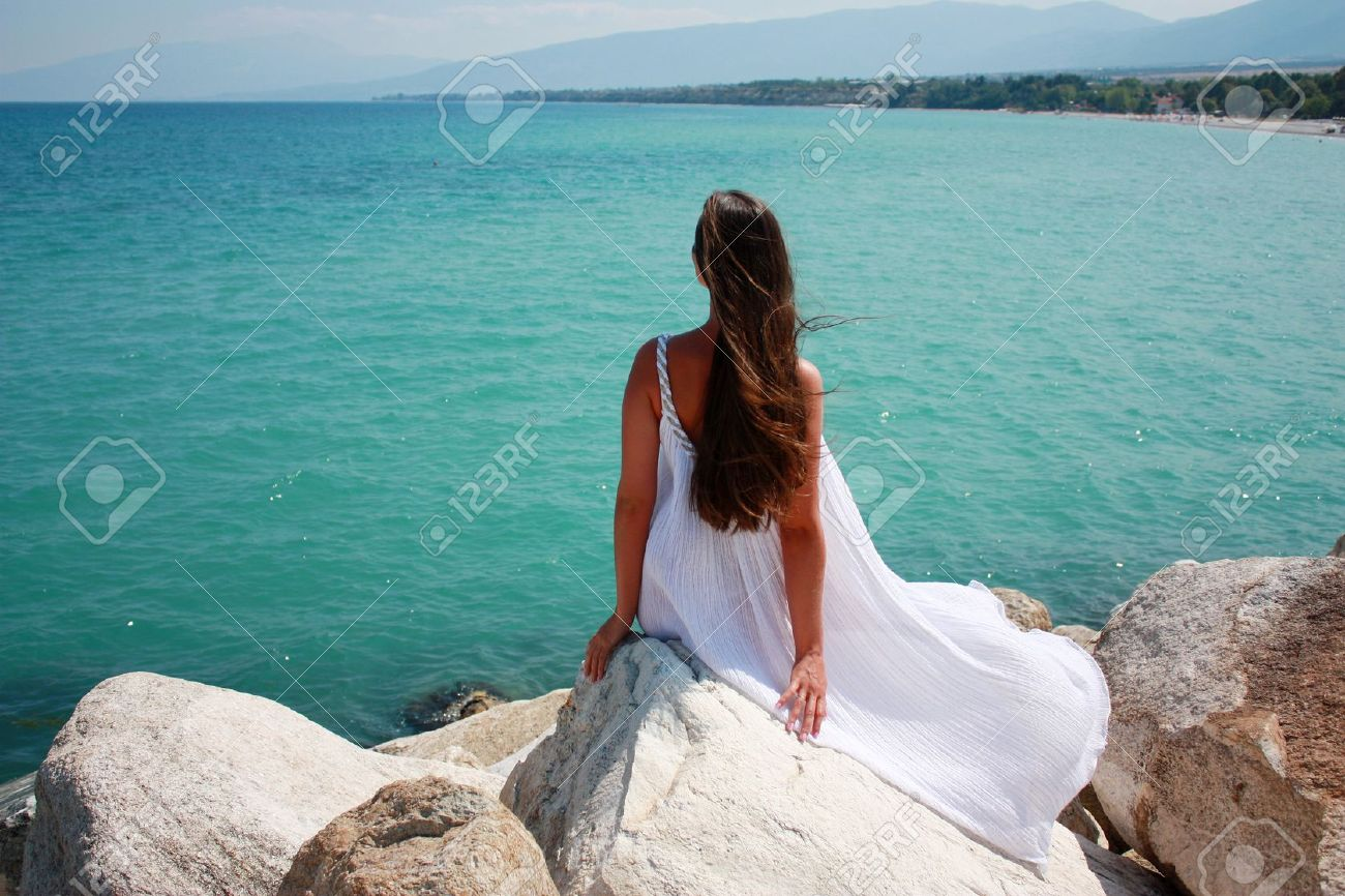Long haired girl in white dress sitting by the sea - 7980770