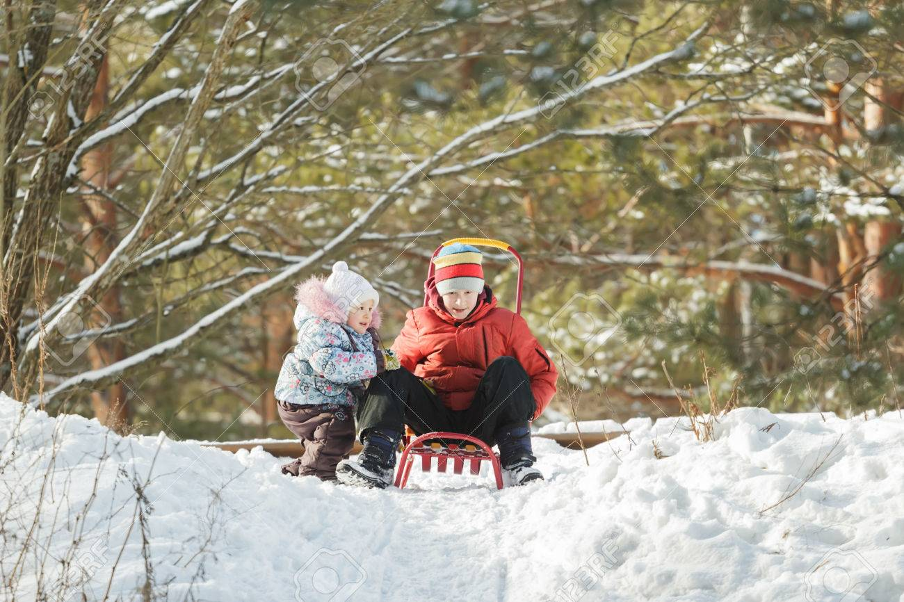 Sibling Children Are Getting Ready For Sliding Down Snowy Hill