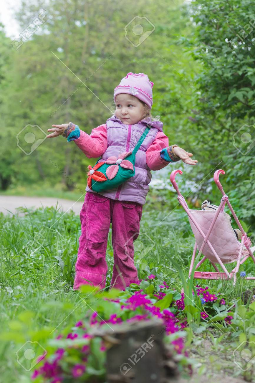 little girl with pink toy stroller is making helpless shrug gesture