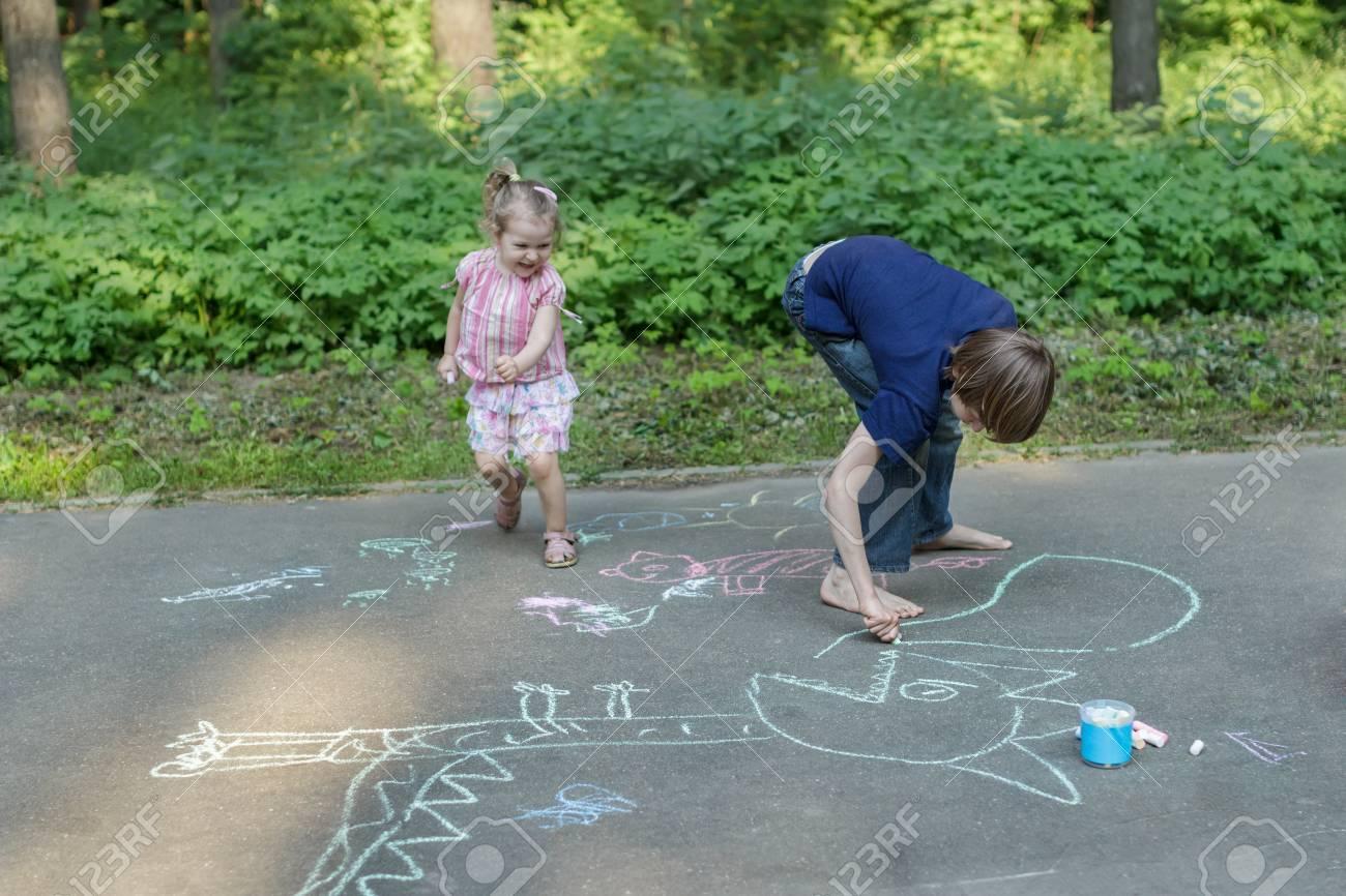Sibling children are having fun during sidewalk chalking on asphalt surface - 58134494