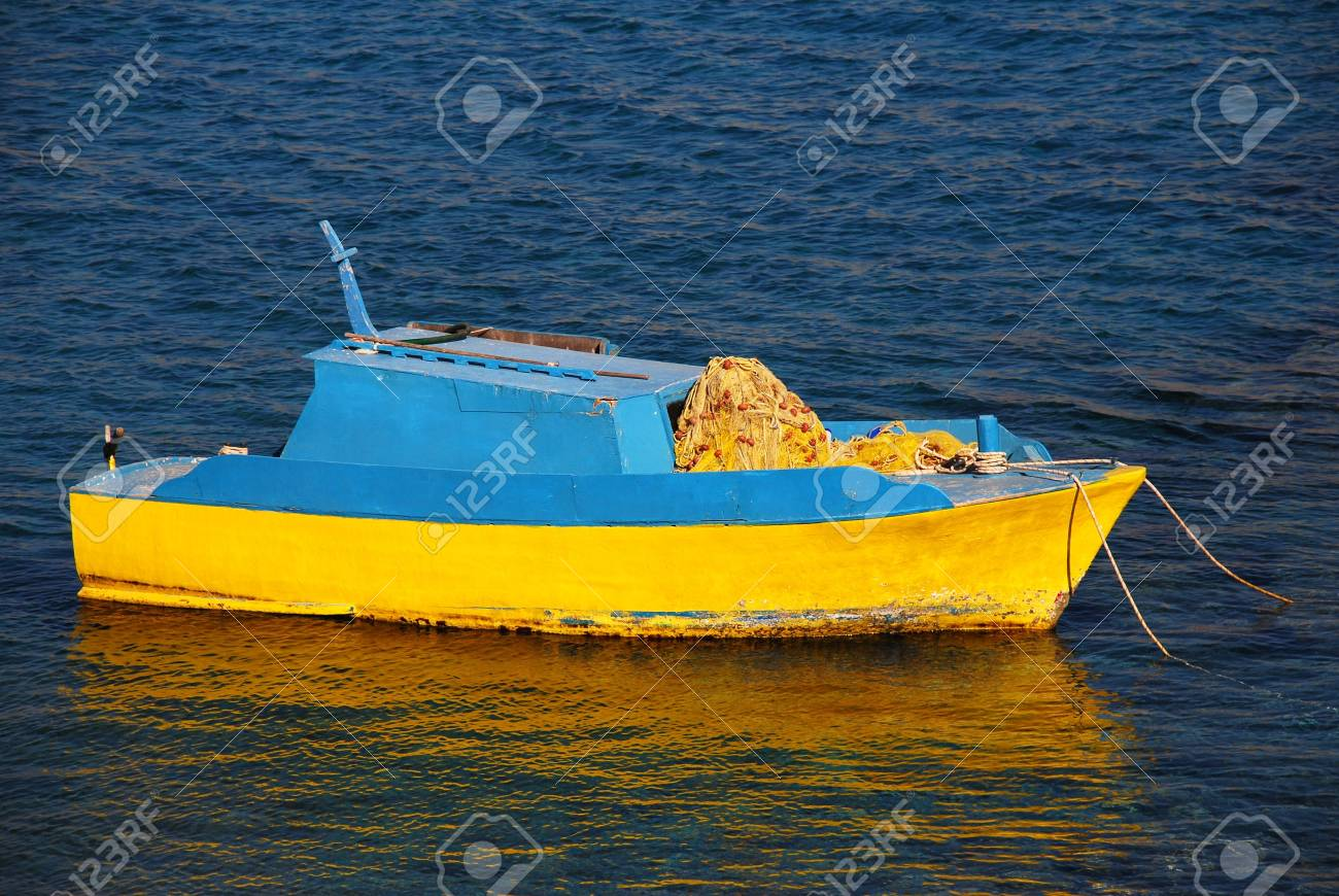 A blue and yellow wooden fishing boat moored off Pondamos beach at Emborio on the Greek island of Halki. Stock Photo - 9195248