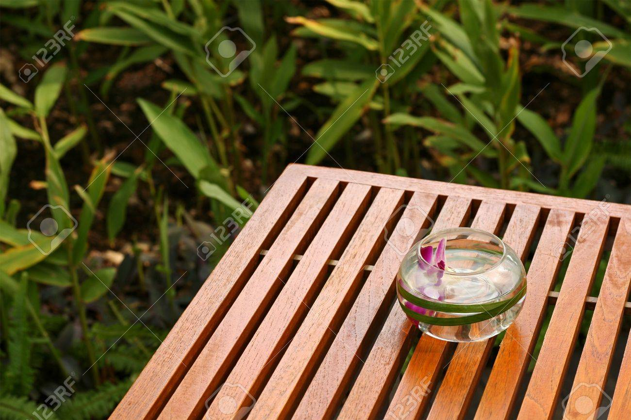orchid flower in a glass bowl decoration set on the wooden