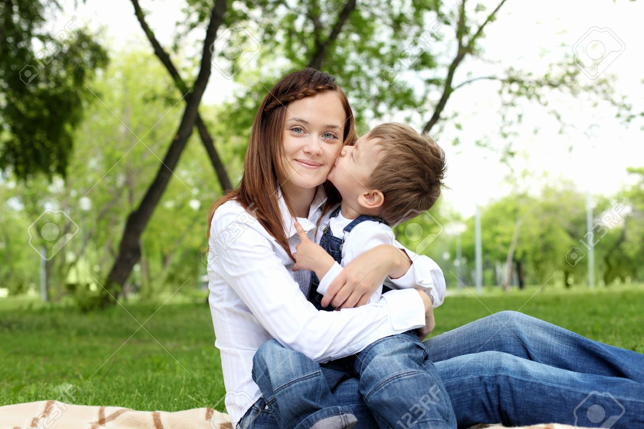 Mother with her son sitting and embracing in the summer park Stock Photo - 12404053