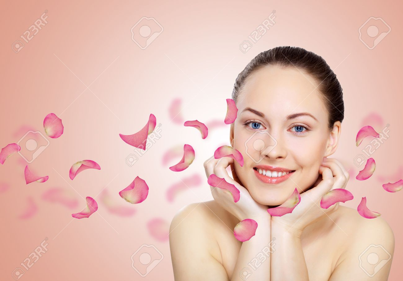 Studio portrait of a beautiful young woman with flowers on background Stock Photo - 13383102