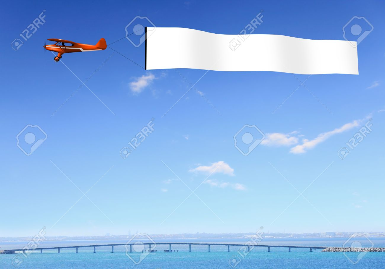 plane in the sky above the city with blank flag stock photo picture
