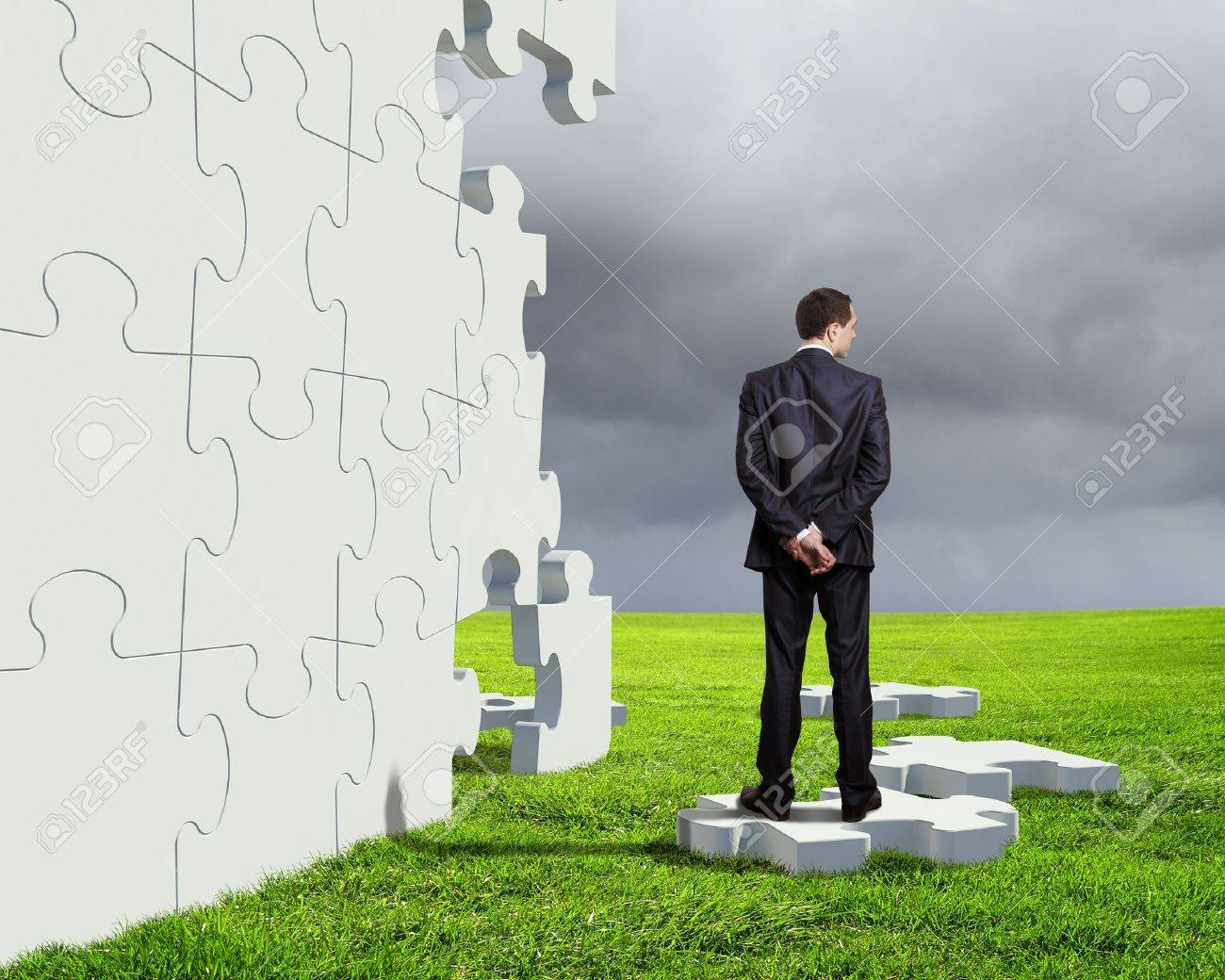 Businessman with a puzzle pieces on the background Stock Photo - 14911709