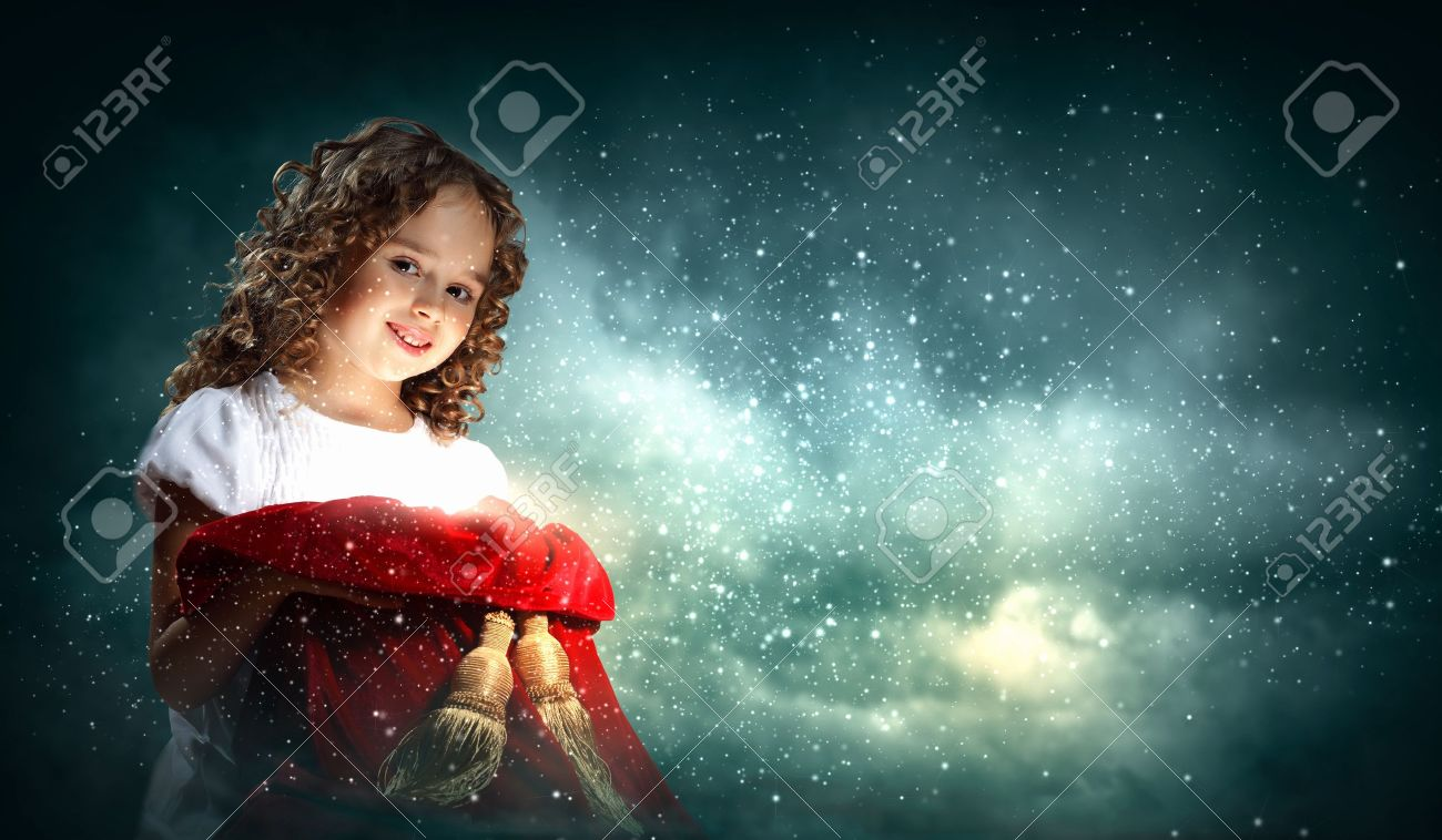 A cute young girl holding a christmas gift, dark background with christmas light bokeh Stock Photo - 15597984