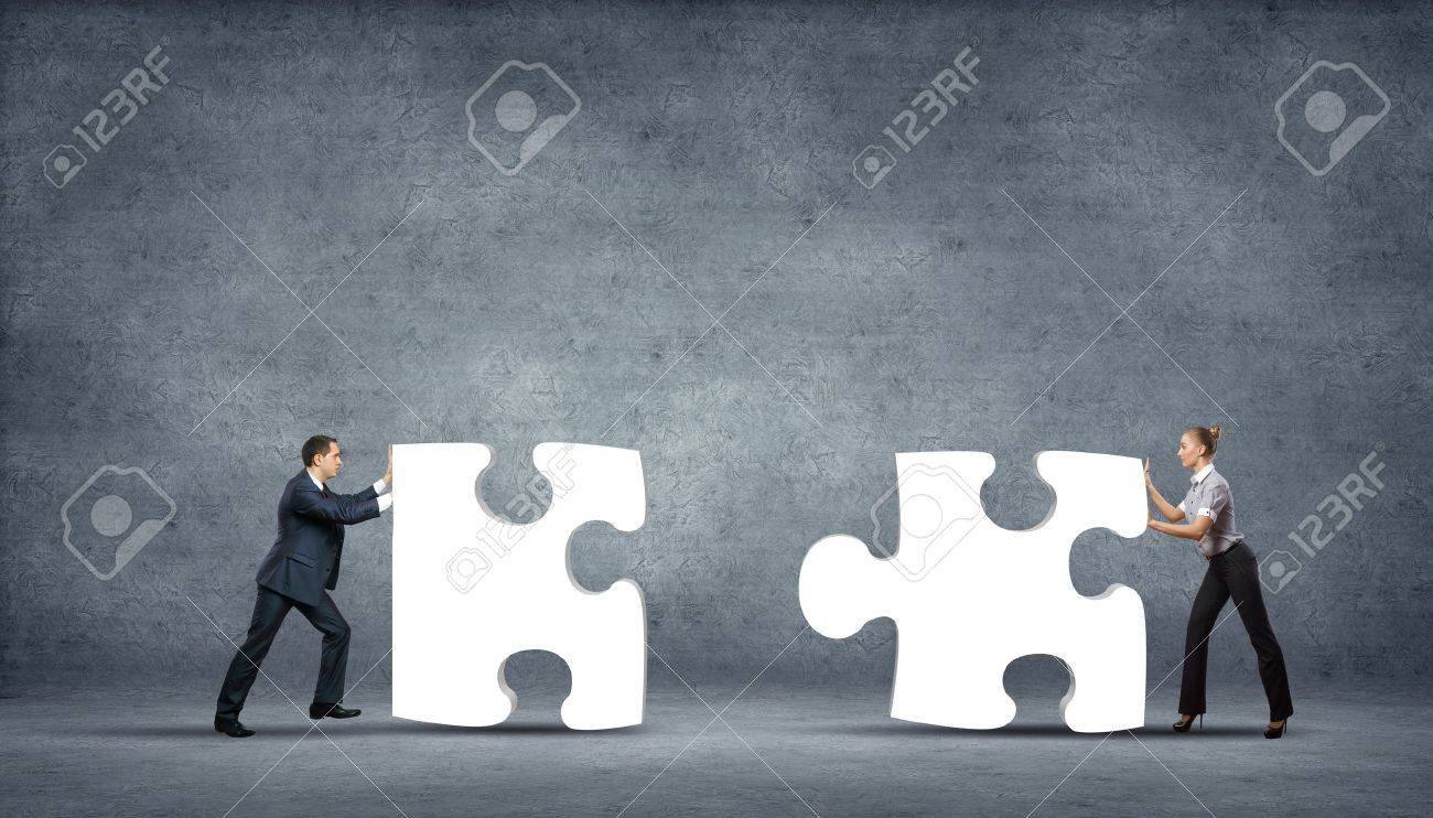 Team of business people collaborate holding up jigsaw puzzle pieces as a solution to a problem Stock Photo - 15743592