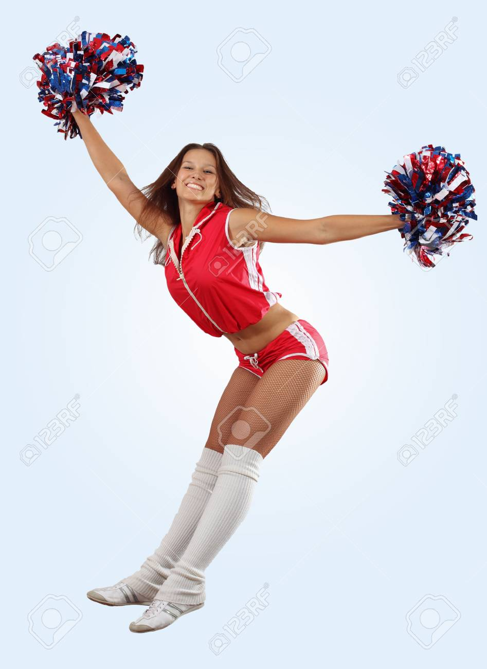 Uniformed cheerleader jumps high in the air 
