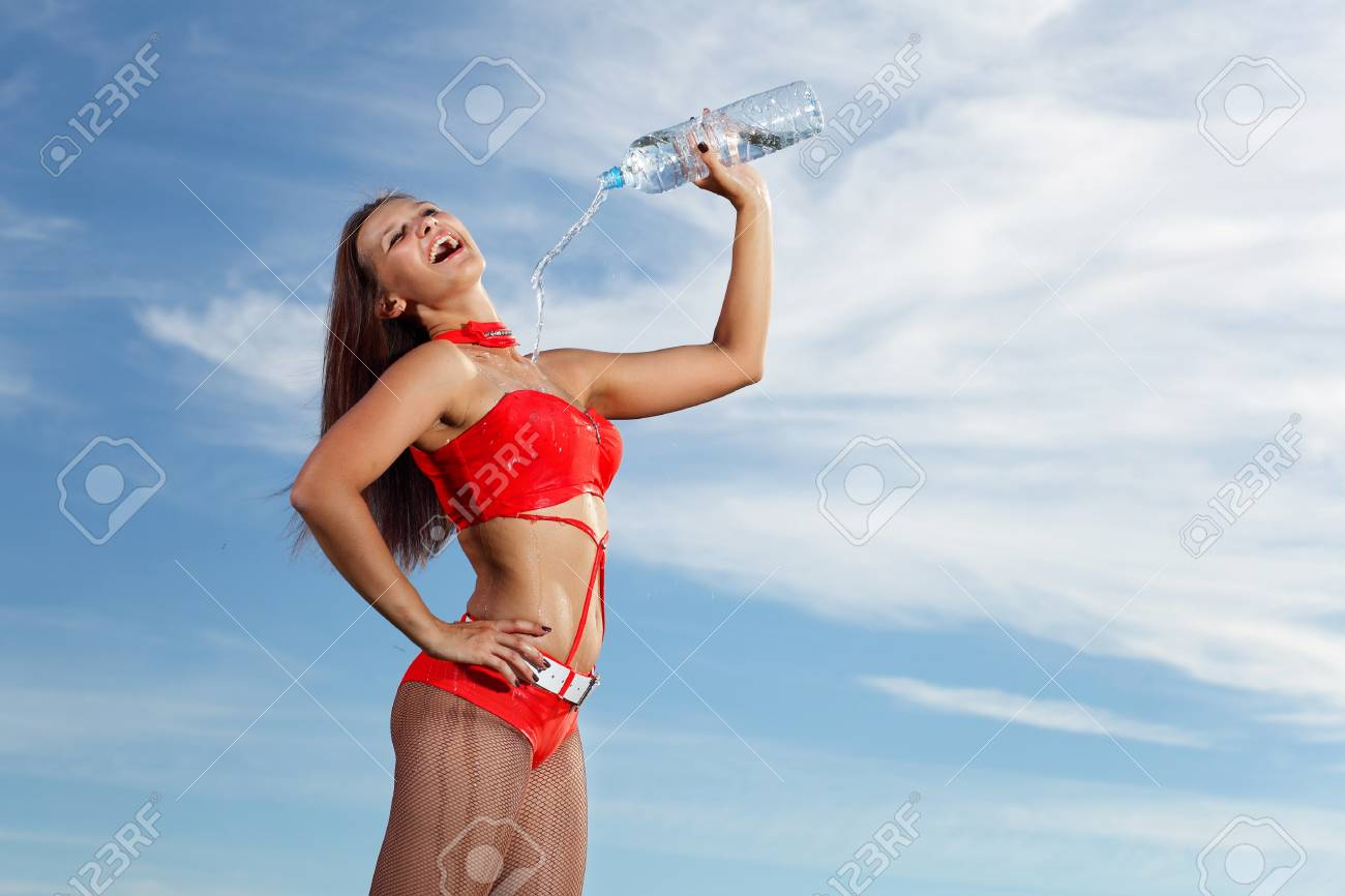 Young female sport girl in red uniform with a bottle of water Stock Photo - 16352684
