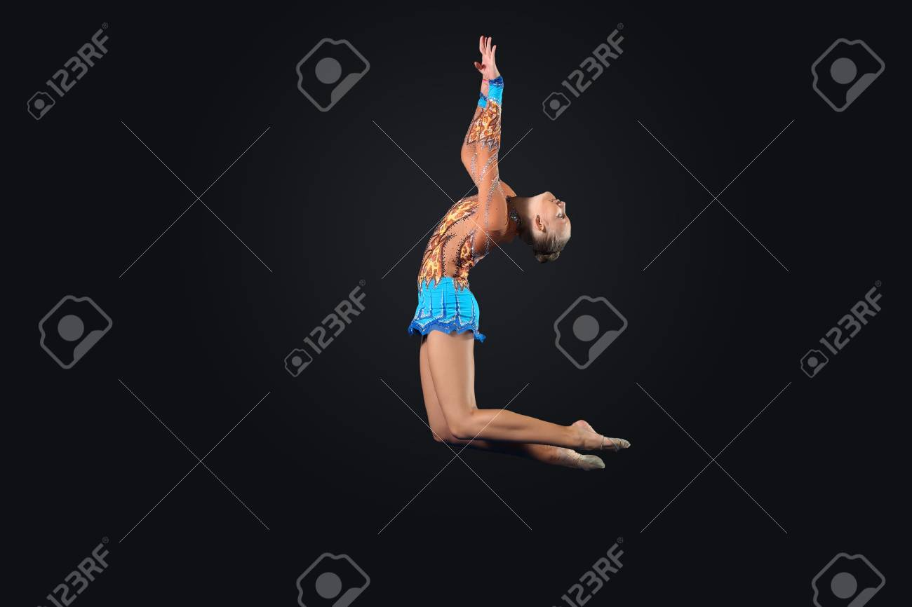 Young cute woman in gymnast suit show athletic skill on black background Stock Photo - 17022039