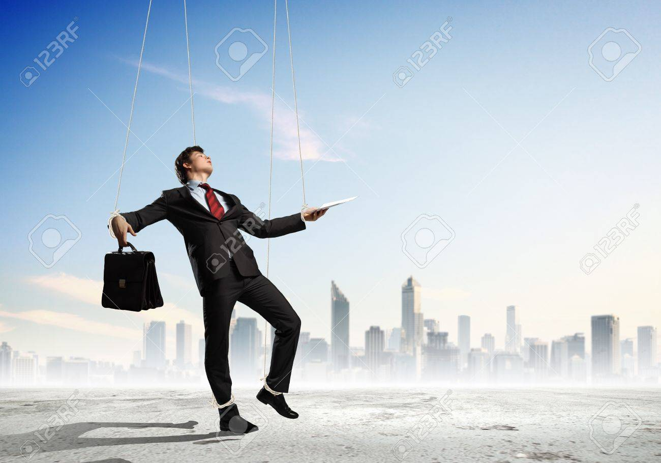 Image of businessman hanging on strings like marionette against city background  Conceptual photography Stock Photo - 17398371