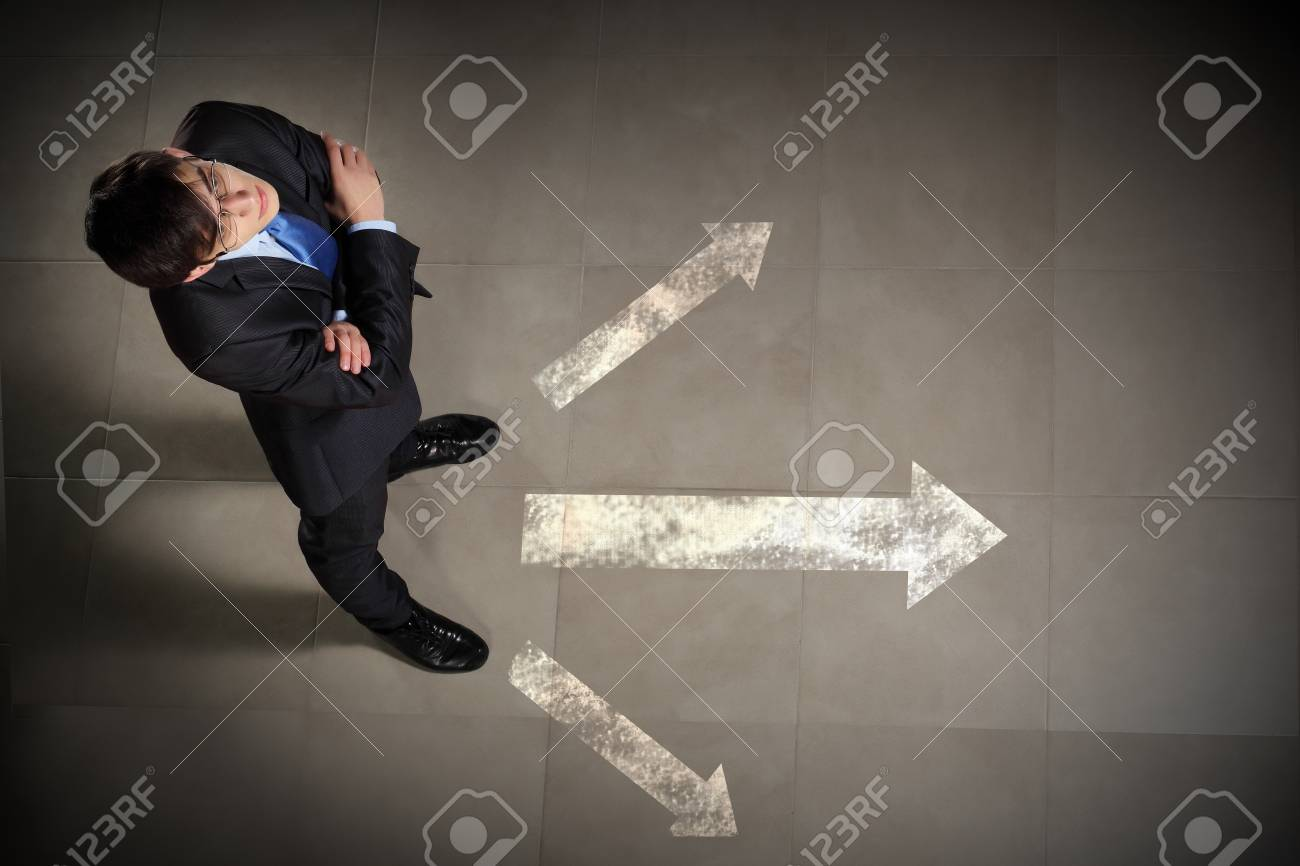 Top view of businessman standing against directions background Stock Photo - 17400517