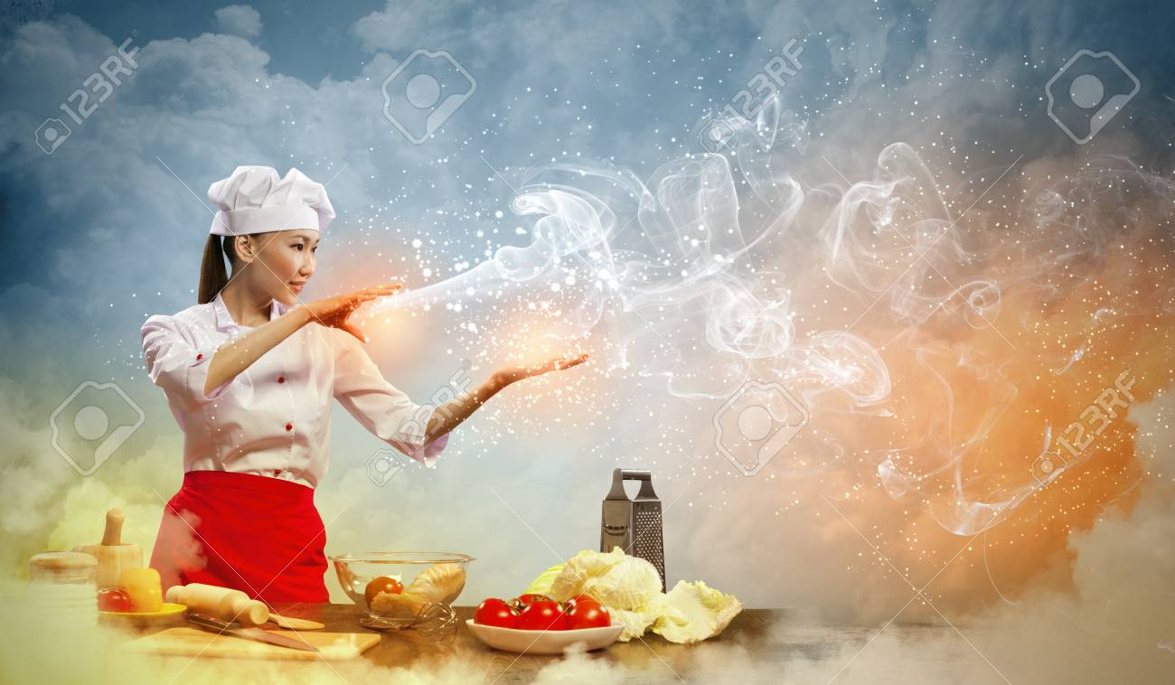 Asian female cooking with magic against color background Stock Photo - 17400085