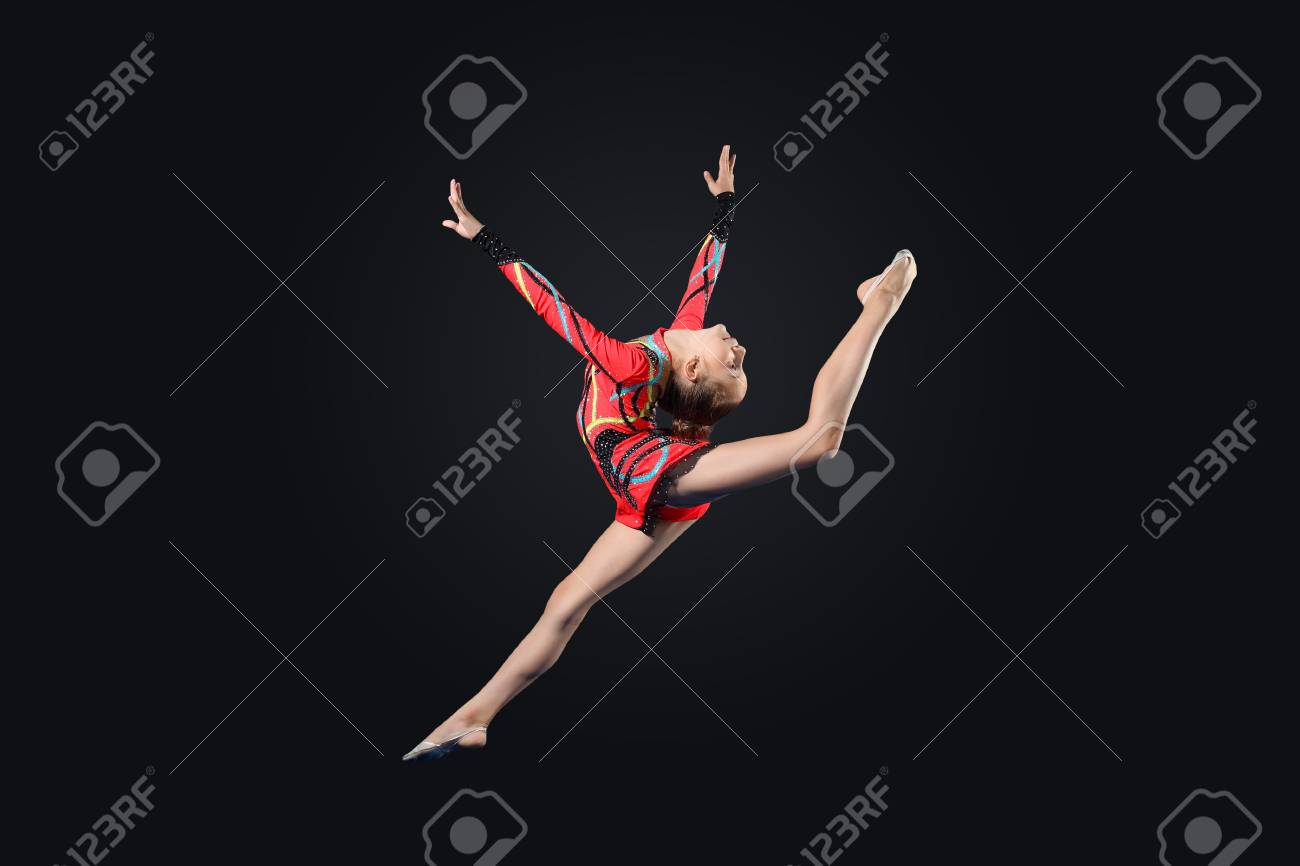 Young cute woman in gymnast suit show athletic skill on black background Stock Photo - 17427316