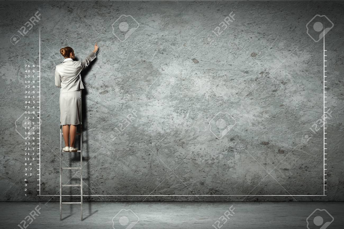 businesswoman standing on ladder drawing diagrams and graphs on wall Stock Photo - 17430962