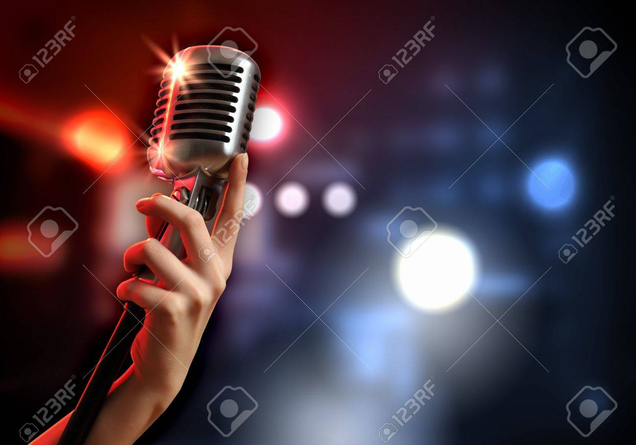 Female hand holding a single retro microphone against colourful background Stock Photo - 17494764
