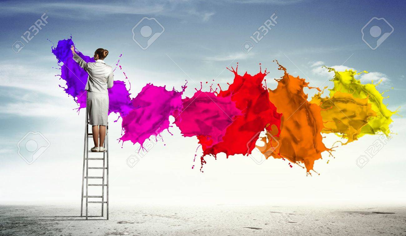 Young woman standing on ladder drawing splashes with finger - 17493820